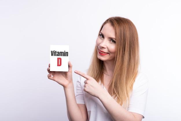 여성 손은 비문 비타민 d가있는 카드를 보여줍니다.