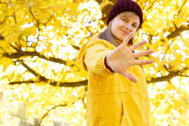 女性の手は秋の背景にぼやけた女性の前で停止を示しています