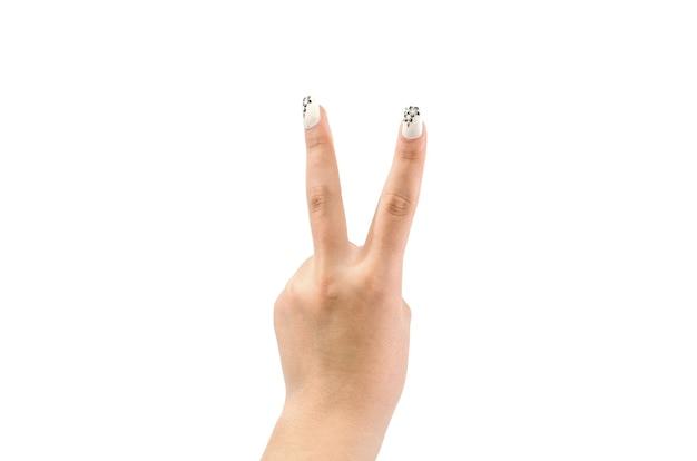 女性の手は白い背景に2本の指を示しています