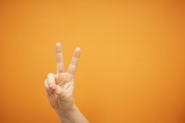 Женская рука показывает знак победы на оранжевом
