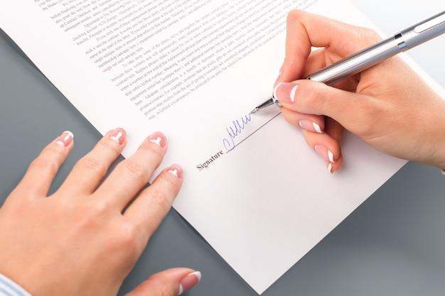 ビジネスペーパーに署名する女性の手。女性の署名文書のクローズアップ。これが最後の言葉です。復帰不能点。