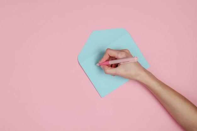 Женская рука подписывает синий конверт на розовом пастельном фоне. тенденция ванильного цвета. вид сверху