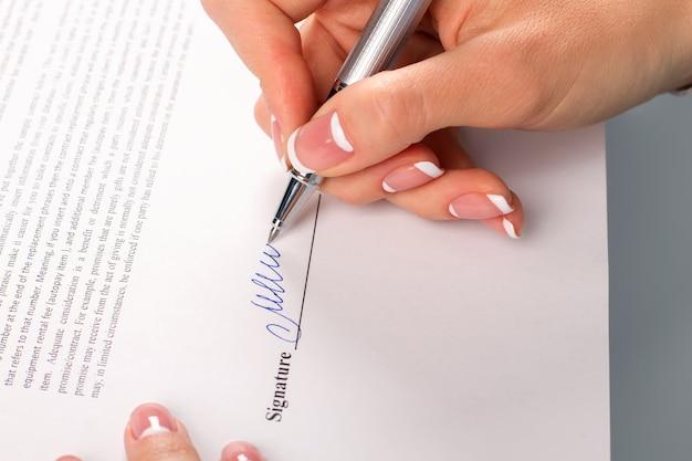 女性の手はビジネスレターに署名します。実業家の署名の手紙のクローズアップ。よろしくお願いします。私のパートナーへの手紙。
