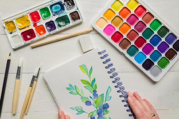 ブルーベリーの枝の水彩画をスケッチする女性の手。水彩絵の具とブラシ、フラットレイ。