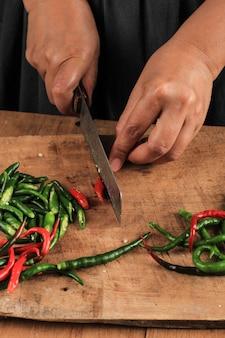 ナイフを使用して木製まな板にカットチリペッパーをスライスする女性