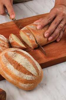 Женская рука нарезает японский хлеб из молочного пода с помощью хлебного ножа на завтрак. milk hearth bread - это японский хлеб с молоком или взбитыми сливками, мягкий и пушистый. выбранный фокус