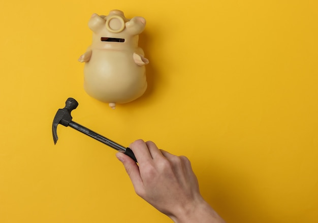 Female hand smashes a piggy bank with a hammer on yellow background minimalistic concept