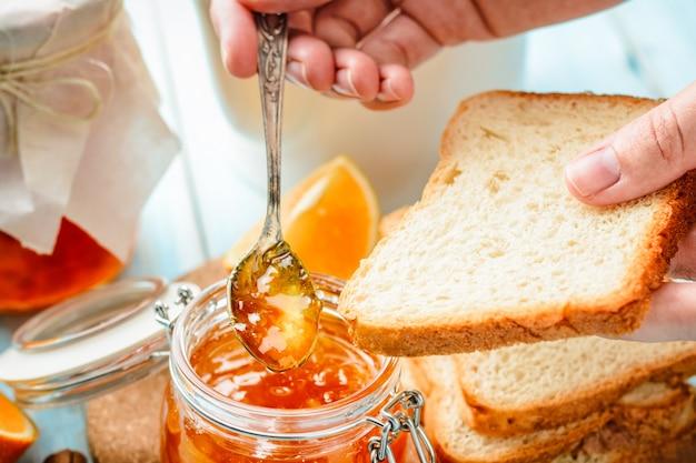 Female hand smears toasts with homemade orange jam