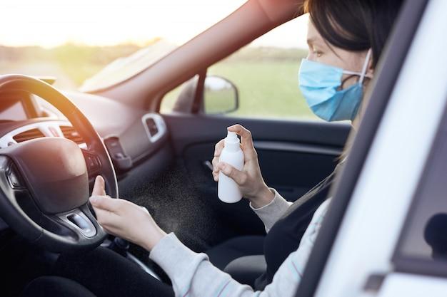 車を消毒するための消毒剤と防腐性ウェットワイプを噴霧する女性の手。コロナウイルス中の清浄度とヘルスケア、covid-19。
