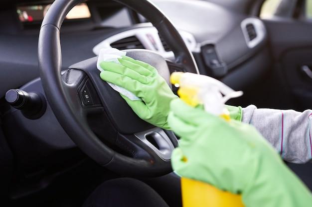 車を消毒するための女性の手スプレー消毒剤と消毒ウェットワイプ。