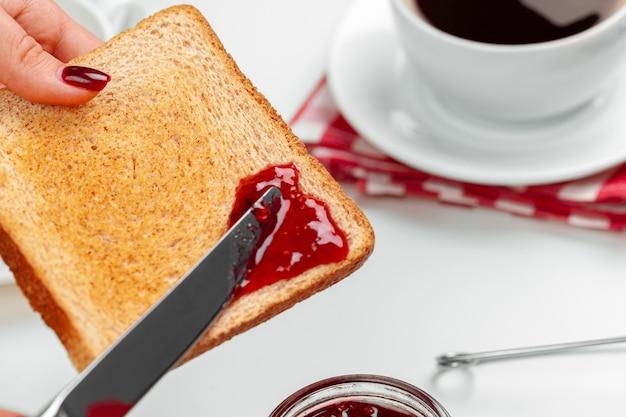 焼きたてのトーストにイチゴジャムを広げる女性の手