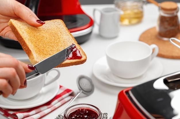 焼きたてのトーストにイチゴジャムを広げている女性の手