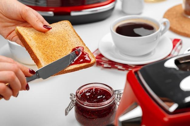 焼きたてのトーストにいちごジャムを振りかける女性の手