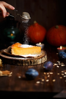 Female hand sprinkles powdered sugar on pumpkin cheesecake.
