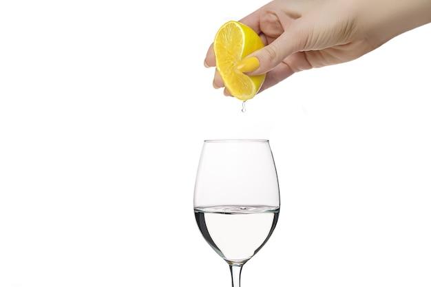 여성의 손은 유리에 레몬을 짜냅니다. 레몬을 짜내는 노란 매니큐어와 여성 손입니다. 레모네이드 준비. 레몬맛 물.