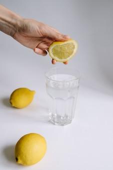 女性の手がレモンジュースをコップ1杯の水に絞りました