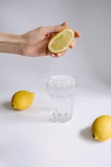 女性の手がレモン汁をコップ一杯の水に絞ります。