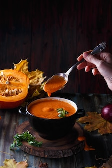 Female hand stir pumpkin soup puree with greens in a plate  table