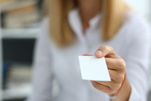 Female hand in suit giving blank card