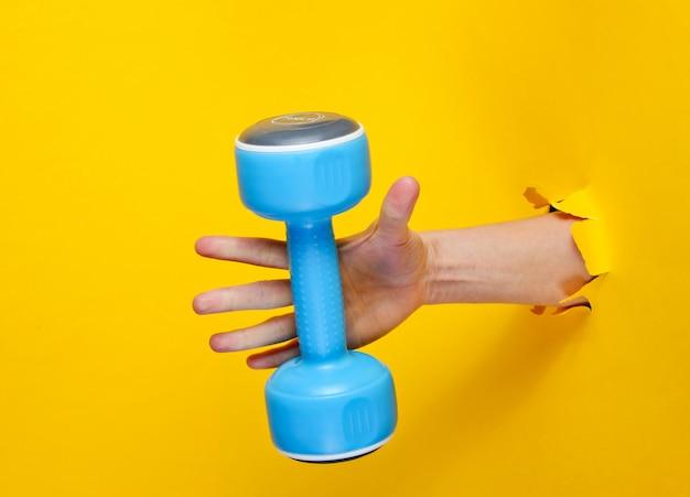 女性の手は引き裂かれた黄色い紙を通して青いプラスチックダンベルを取ります。ミニマルスポーツコンセプト