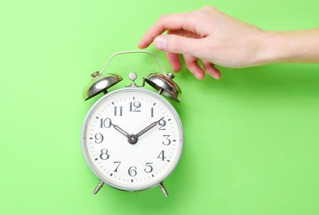 女性の手は緑の背景に目覚まし時計を取ります