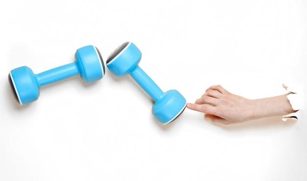 Женская рука берет голубую пластиковую гантель через рваную белую бумагу. минималистичная спортивная концепция