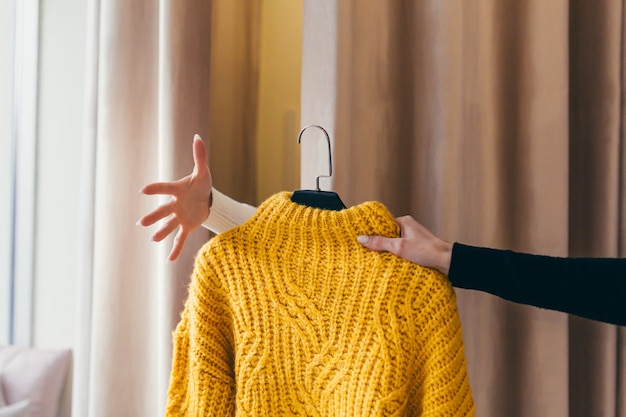 Женская рука берет одежду для примерки в магазине