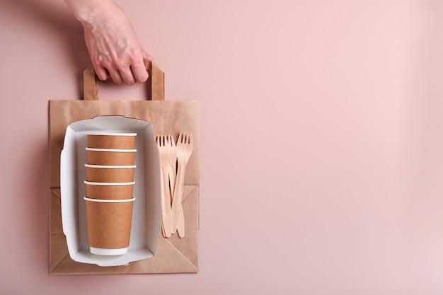 여성의 손은 컵, 접시, 나무 포크, 빨대, 패스트푸드 용기, 분홍색 배경에 나무 칼이 든 종이 봉지를 가져갑니다. 에코크래프트 종이 식기. 재활용 개념입니다. 조롱. 평면도