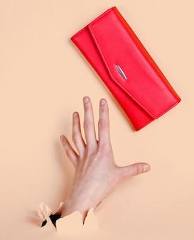 여성 손은 찢어진 된 노란색 파스텔 종이를 통해 빨간색 지갑을 걸립니다. 미니멀리즘 창의적인 패션 컨셉