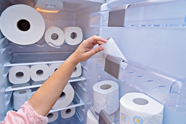 Женская рука берет рулон туалетной бумаги с двери холодильника