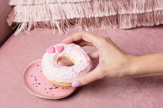 Female hand takes a sweet pink donut on pink