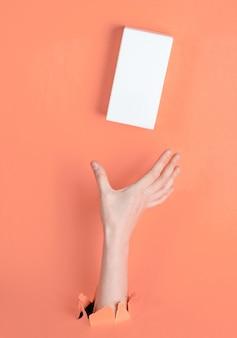 Женская рука берет белую коробку через разорванную розовую бумагу. минималистичная креативная концепция моды