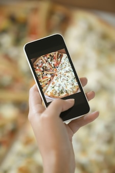 Female hand taking a picture of pizza