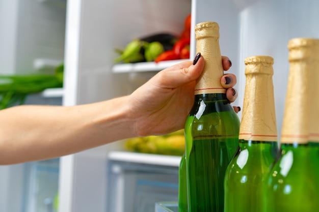 冷蔵庫からビールのボトルを取っている女性の手がクローズアップ