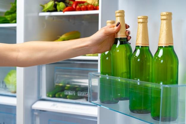 冷蔵庫からビールのボトルを取る女性の手