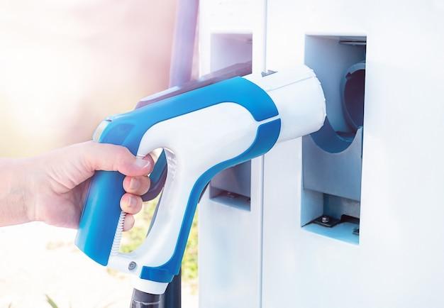 Женская рука берет на себя ответственность за электромобили на открытом воздухе. экологичный
