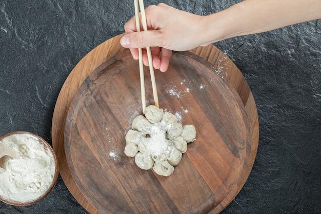 プレートから箸で餃子を取る女性の手。