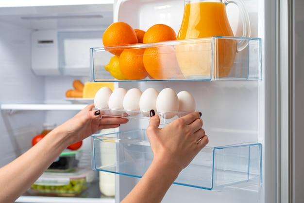 Female hand taking egg from a fridge