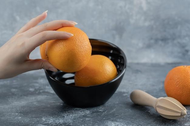 Mano femminile che prende arancia fresca dalla ciotola nera.