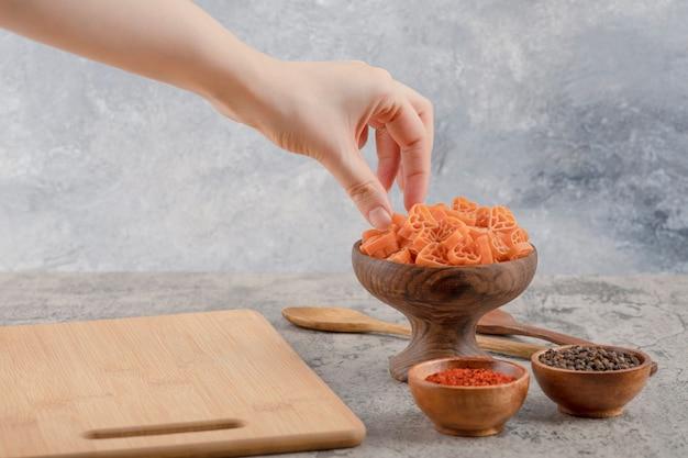 Женская рука берет макароны из деревянной миски на мраморном фоне