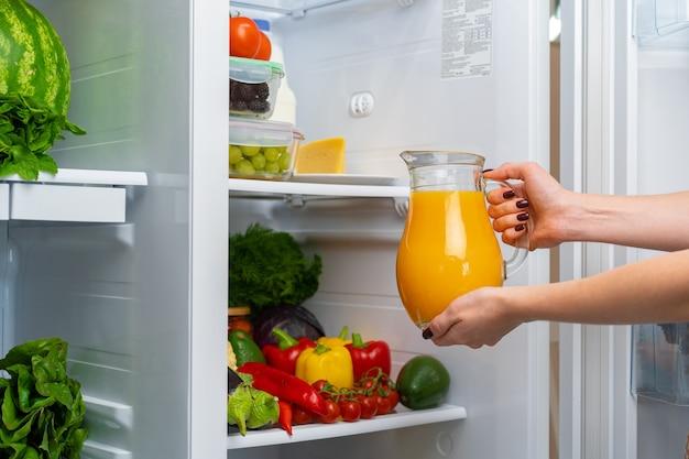 Female hand taking orange juice jar from a fridge