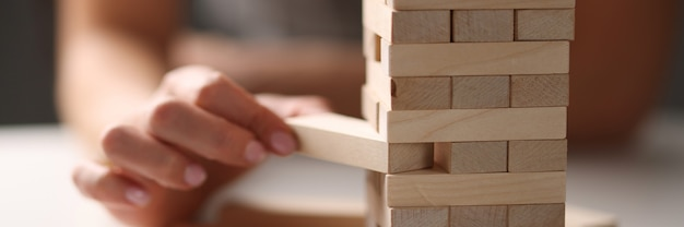 Female hand taking out block from wooden tower closeup. table games concept