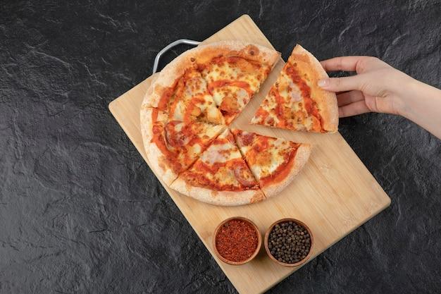 Mano femminile che prende un pezzo di pizza di bufala dal bordo di legno.