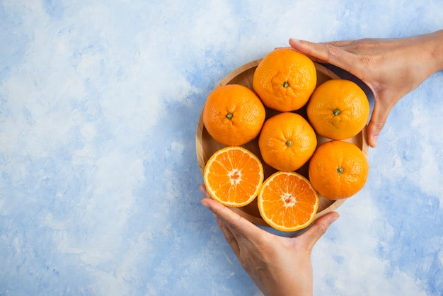 Mano femminile che cattura fetta dal mucchio. mandarini clementine sulla superficie blu