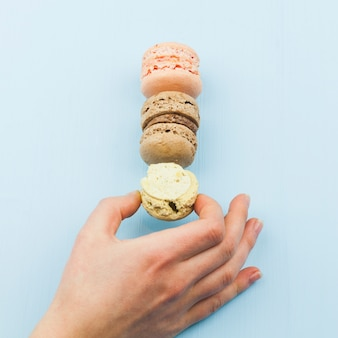 Female hand taking tasty macaroons