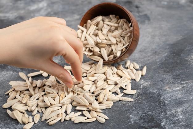 흰색 해바라기 씨앗을 복용하는 여성 손 대리석 표면에 흩어져.