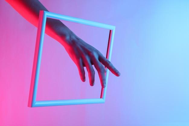 ネオンホログラフィックライトで高騰フレームを介して女性の手