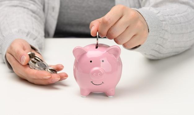 女性の手が白いテーブルの上のピンクの貯金箱にコインを投げます。現金の蓄積、貯蓄、補助金の受け取りの概念