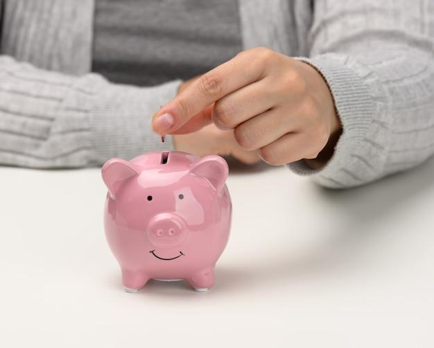 여성 손은 흰색 탁자에 있는 분홍색 돼지 저금통에 동전을 던졌습니다. 현금 축적, 저축, 보조금 수령의 개념