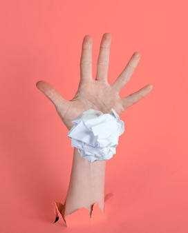 女性の手は、引き裂かれたピンクの紙の背景に紙のしわくちゃのボールを投げます。ミニマルなアイデアの概念